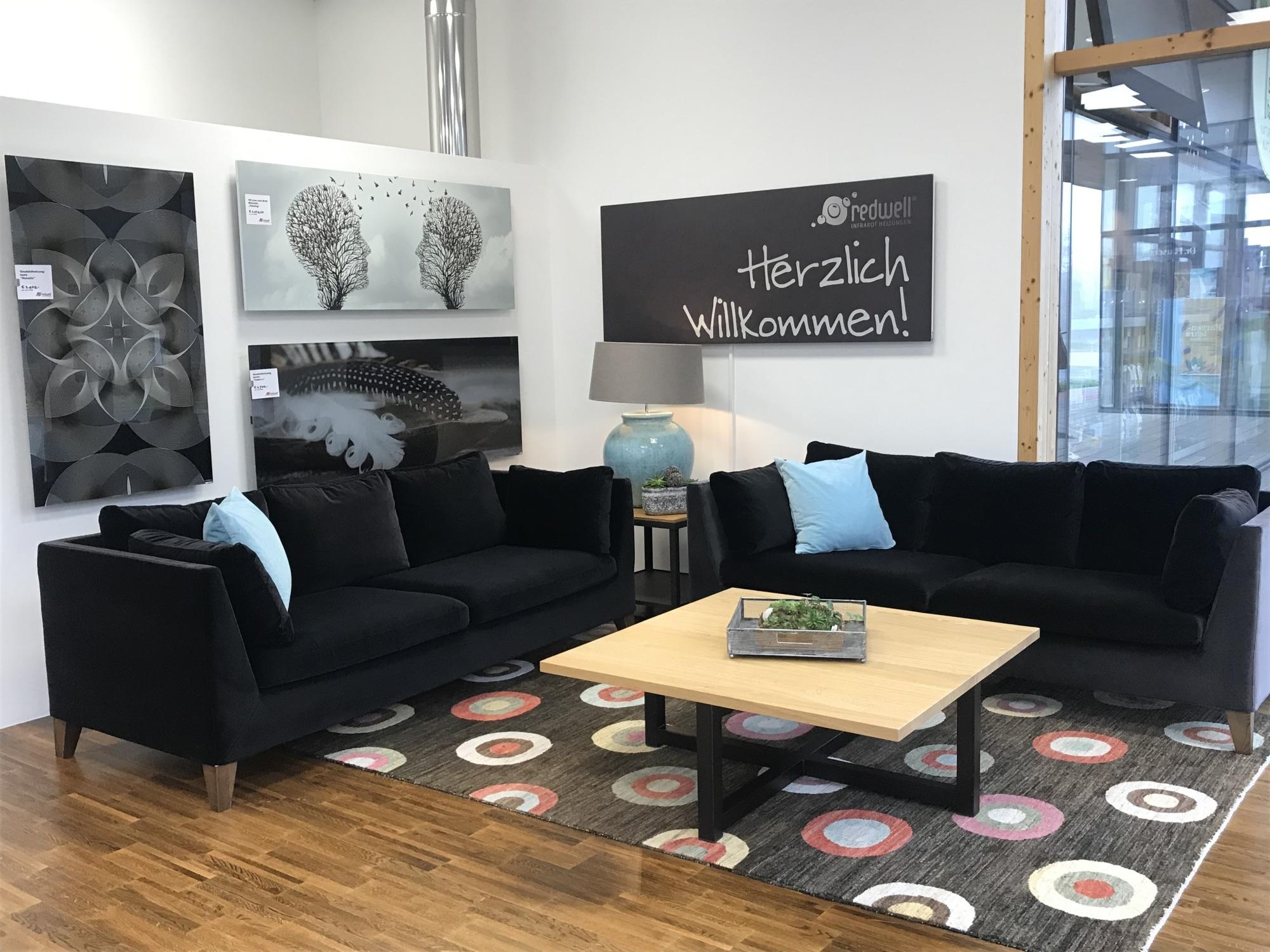 Der Eingangsbereich des neuen Redwell Flagship-Stores in Hartberg mit schwarzen Sofas und Infrarotbildheizungen.
